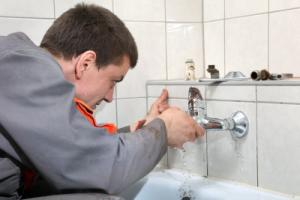 a technician fixes a leaky bathtub spout